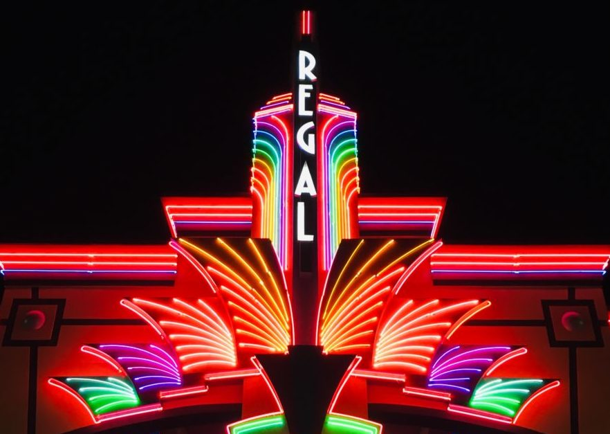 A movie theater with gaudy neon signs.